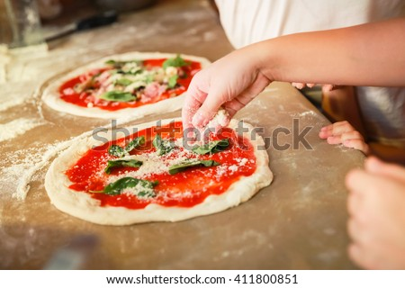 Preparing Pizza Margherita, the archetype of Neapolitan pizza. Cook adds grated parmesan cheese. Selective focus