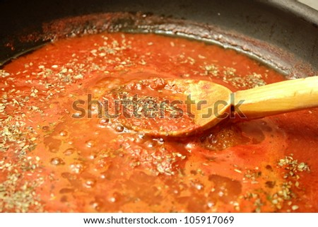 preparing pizza sauce with a wooden spoon - stock photo