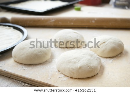 preparing pizza with balls of  dough with flour and rolling on a table