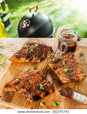 Preparing ribs for a BBQ with savory basting sauce and finely chopped fresh herbs with three portions on a table with a jar of marinade and a brush - stock photo
