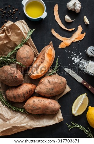 Preparing rosemary roasted sweet potatoes with olive oil, lemon, salt, pepper and garlic - kitchen scenery from above. Black chalkboard as background. Dark moody style. - stock photo