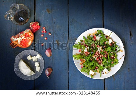 preparing salad with arugula, feta cheese, pomegranate, garlic and balsamic dressing served on a white plate on an old blue wooden table, view from above - stock photo