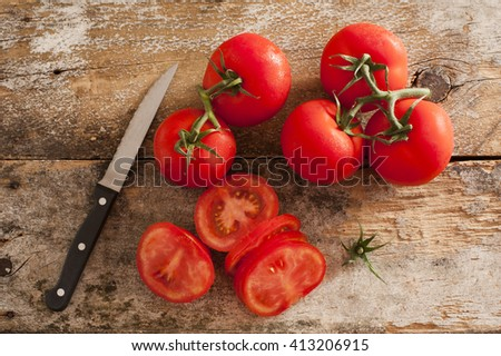 Preparing sliced ripe red tomatoes on a rustic wooden kitchen counter with a paring knife, overhead view of sliced and whole tomatoes on the vine - stock photo