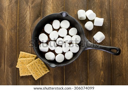 Preparing smores dip prepared with large marshmallows in cast iron pan.
