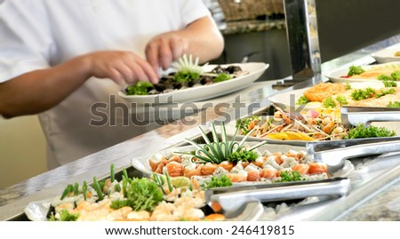 PREPARING SUSHI 1 - A shallow depth of field image looking along a sushi buffet bar - stock photo