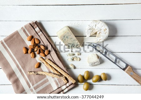 Preparing Tasty Snack With Blue Cheese, Goat Cheese And Olives - stock photo