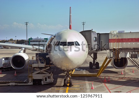 Preparing the aircraft for takeoff, Istanbul Ataturk Airport. The front part of air plane with cockpit standing at ramp. Airplane at docking tunnel.  - stock photo