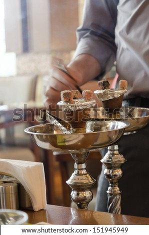 Preparing the shisha, aka nargile or hookah at a restaurant by placing the charcoals on top. A very middle eastern custom. - stock photo
