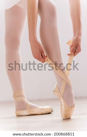 Preparing to dance. Close-up of ballerina tying her slippers while standing on hardwood floor