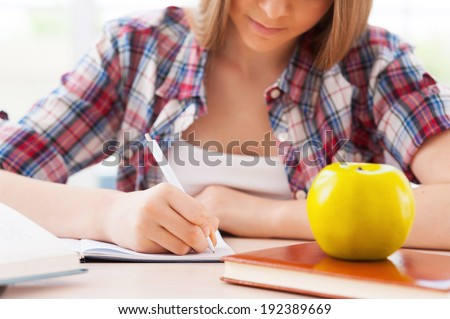 Preparing to exams. Cropped image of confident teenage girl studying while sitting at the desk - stock photo