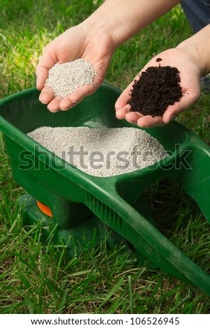 Preparing to fertilize lawn in back yard in spring time - stock photo