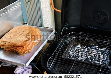 Preparing to grill sliced sheets of dried and crispy pork. Chinese people like to make them and it is one of favorite food for Chinese people