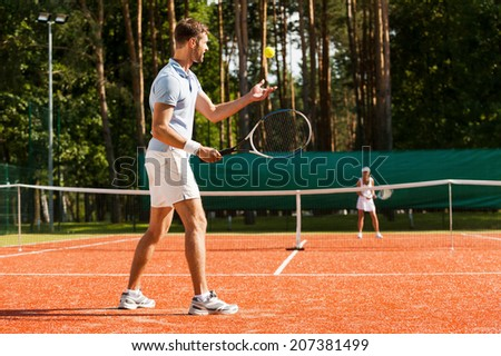 Preparing to his best serve. Full length of man and woman playing tennis on tennis court  - stock photo
