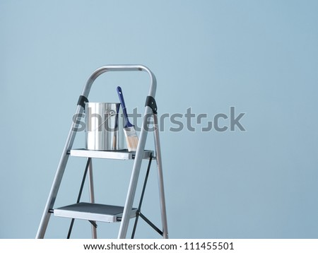 Preparing to paint the wall. Painting tools on a metal ladder. - stock photo