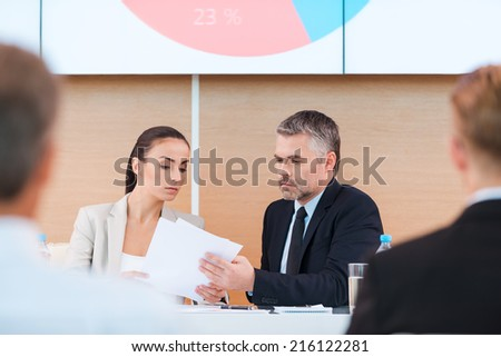 Preparing to presentation. Confident mature man and woman in formalwear sitting at the table and looking at paper with large monitor upon his head and people on foreground  - stock photo