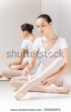Preparing to show her best. Beautiful young ballerina in white tutu sitting against a mirror and tying her slippers