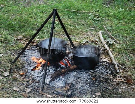 Preparing touristy food on campfire in wild camping - stock photo