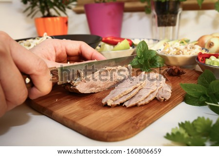 Preparing Vietnamese rice noodles with beef: cutting cooked beef - stock photo