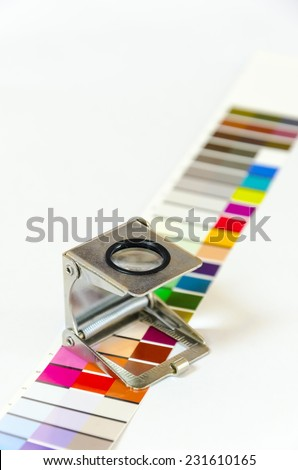 Prepress color menagement in print production. CMYK color check on printed paper. Quality printing concept. - stock photo