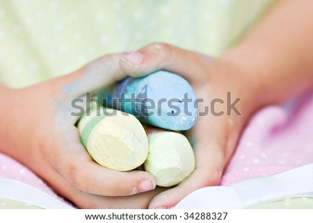 Preschool age child holding colored chalk in her hands.