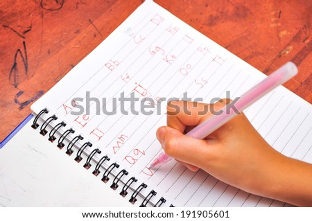 Preschool age child writing alphabet, close up of hands and paper - stock photo