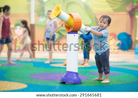 Preschool aged boy playing in water park. Happy young boy has fun playing with water toy.