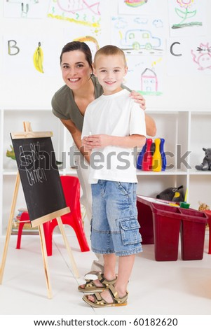 preschool boy and teacher in front of black board in classroom - stock photo