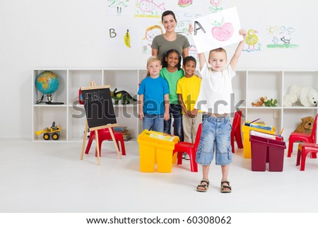preschool boy holding his painting in front of class