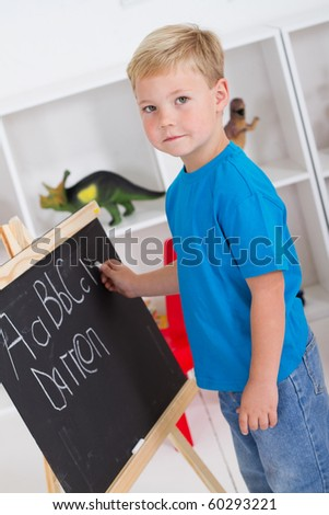 preschool boy in front of blackboard - stock photo