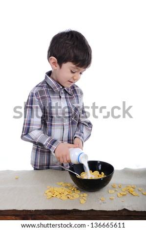 Preschool boy is preparing is breakfast of corn flakes and milk - stock photo
