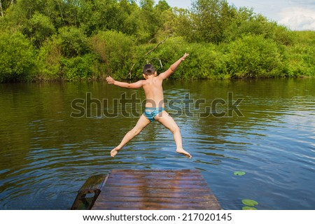 Preschool boy jumping into the river - stock photo