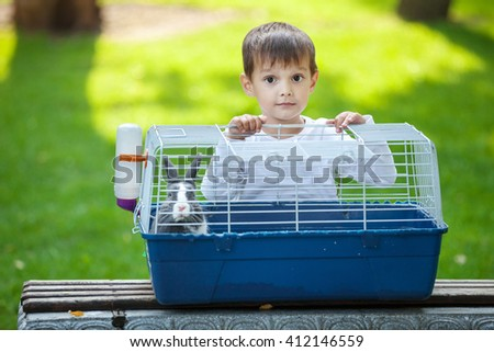 Preschool boy opening a cage with a pet rabbit in a park - stock photo