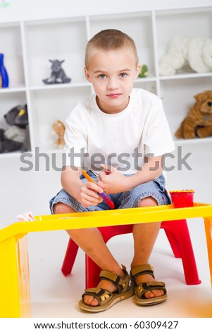preschool boy paint in classroom - stock photo