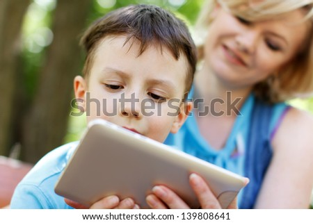Preschool boy playing on tablet with mother, nature - stock photo