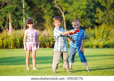 Preschool boy throwing frisbie, his friends looking beside - stock photo