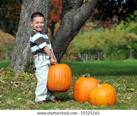 Preschool boy working hard to pick up the heaviest of his family's 3 pumpkins.