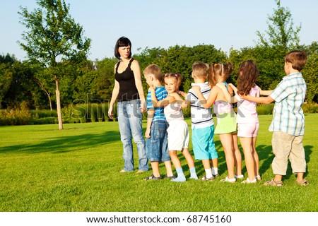 Preschool boys and girls following their teacher - stock photo