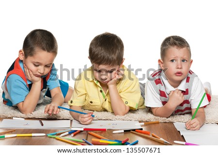 Preschool  boys are lying on the floor and drawing on paper - stock photo