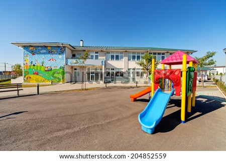 Preschool building exterior with playground on a sunny day - stock photo