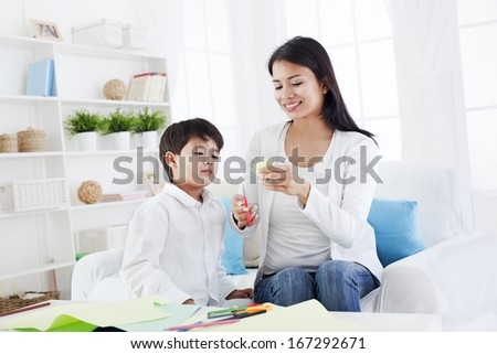 Preschool child and his mother cutting craft in their living room . Mother is helping her son to learn art.Also can be used as a teacher and student - stock photo
