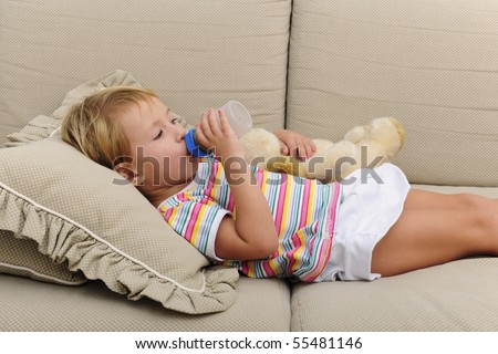 Preschool child drink a baby bottle with milk and chocolate, lay on the couch