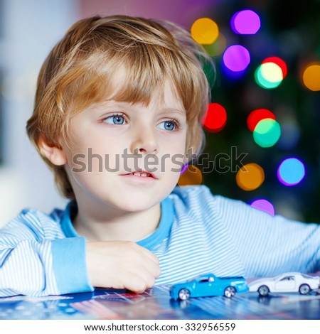 Preschool child playing with cars and toys at home, indoor. funny boy having fun with gifts. Colorful christmas lights on background. Family, holiday, kids lifestyle conceplt. - stock photo