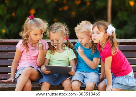 Preschool Children are sitting on a bench at the park - stock photo