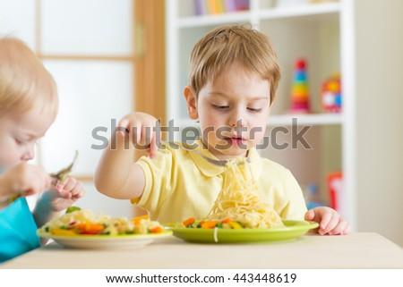 Preschool children eat healthy food in kindergarten or home - stock photo