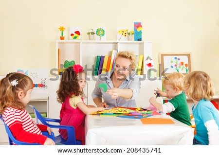 Preschool children in the classroom with the teacher - stock photo