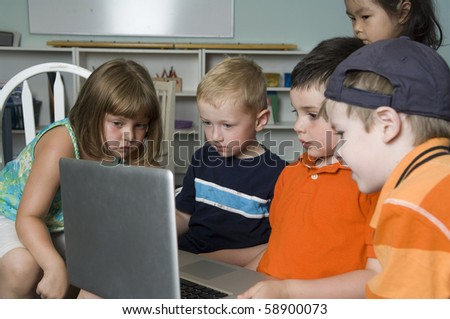 Preschool children play and learn while using a laptop computer in their class.