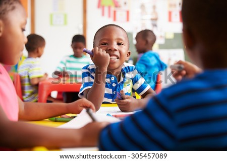 Preschool class in South Africa, boy looking to camera - stock photo