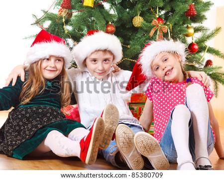 Preschool friends sitting under Christmas tree - stock photo