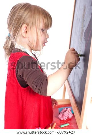 preschool girl in red dress drawing on blackboard - stock photo