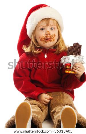 Preschool girl in santa hat eating chocolate - stock photo